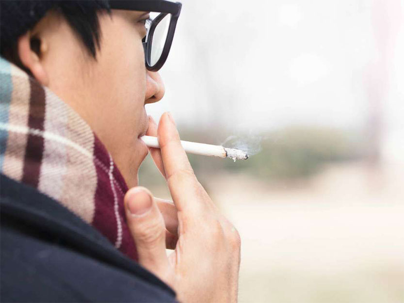 photo of man with eyeglasses smoking